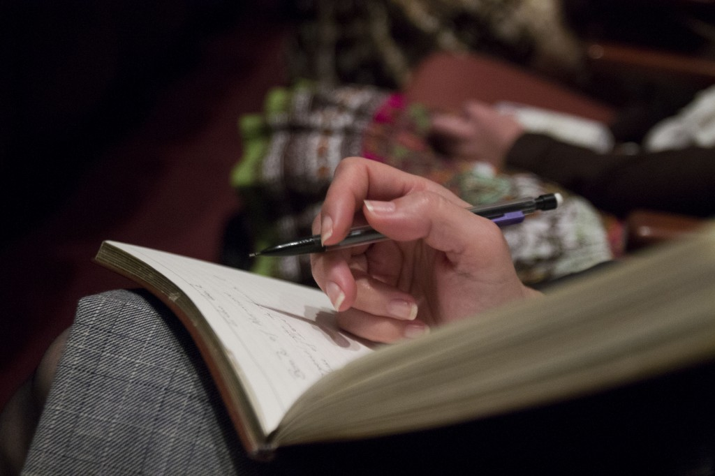 A woman takes notes during General Conference. Taking notes is one way to remember thoughts and impressions that occur while watching General Conference. RACHAEL ANTHONEY | Scroll Photography