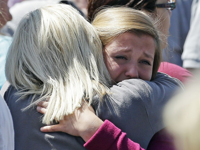 Freshman Hailee Siebert, 15, cries on her mothers shoulder after students arrived at a shopping center parking lot in Wood Village, Ore., after a shooting at Reynolds High School Tuesday, June 10, 2014, in nearby Troutdale. A gunman killed a student at the high school east of Portland Tuesday and the shooter is also dead, police said. (AP Photo/Rick Bowmer)
