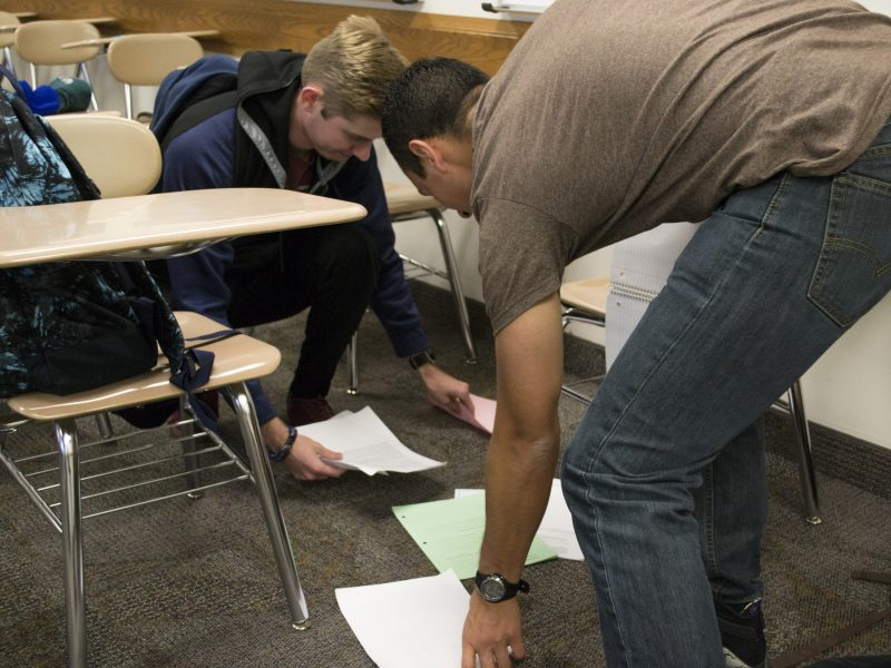 A student receives help picking up dropped papers. (Samantha Vanderwalker, Scroll)