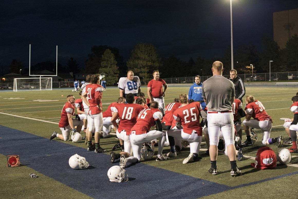 Football team finish's off the day by listening to their coach (Logan Peterson, Scroll Photography)