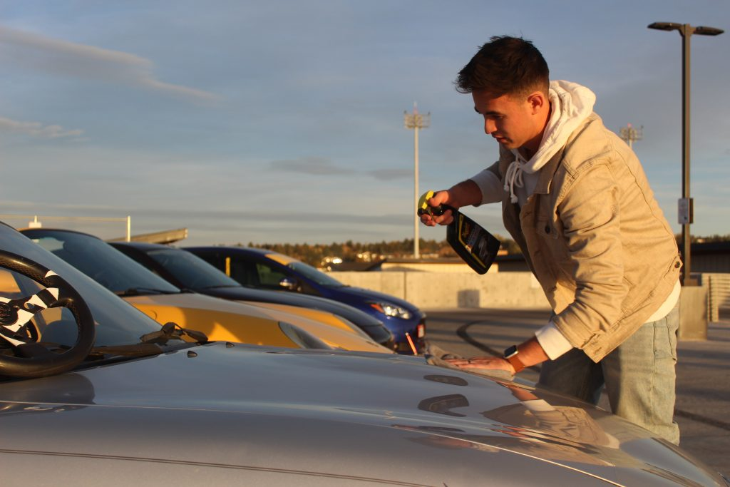 Loren Clifford wiping the hood of his second generation Mazda Miata