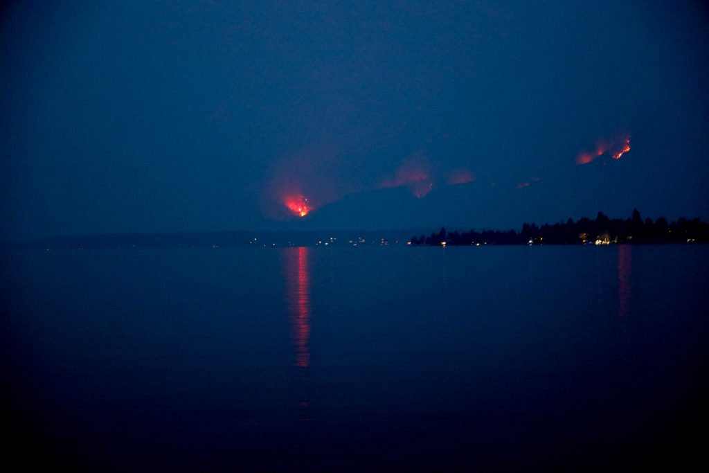 Late at night, fires can be seen in the mountain across the lake.