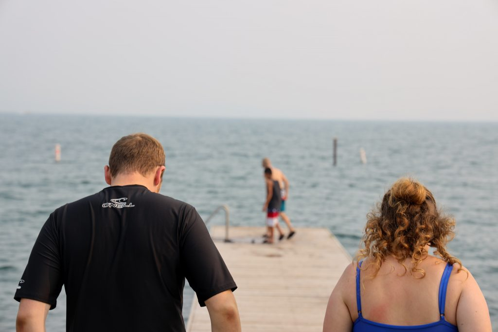 Families enjoy their time at the lake, playing in the water.