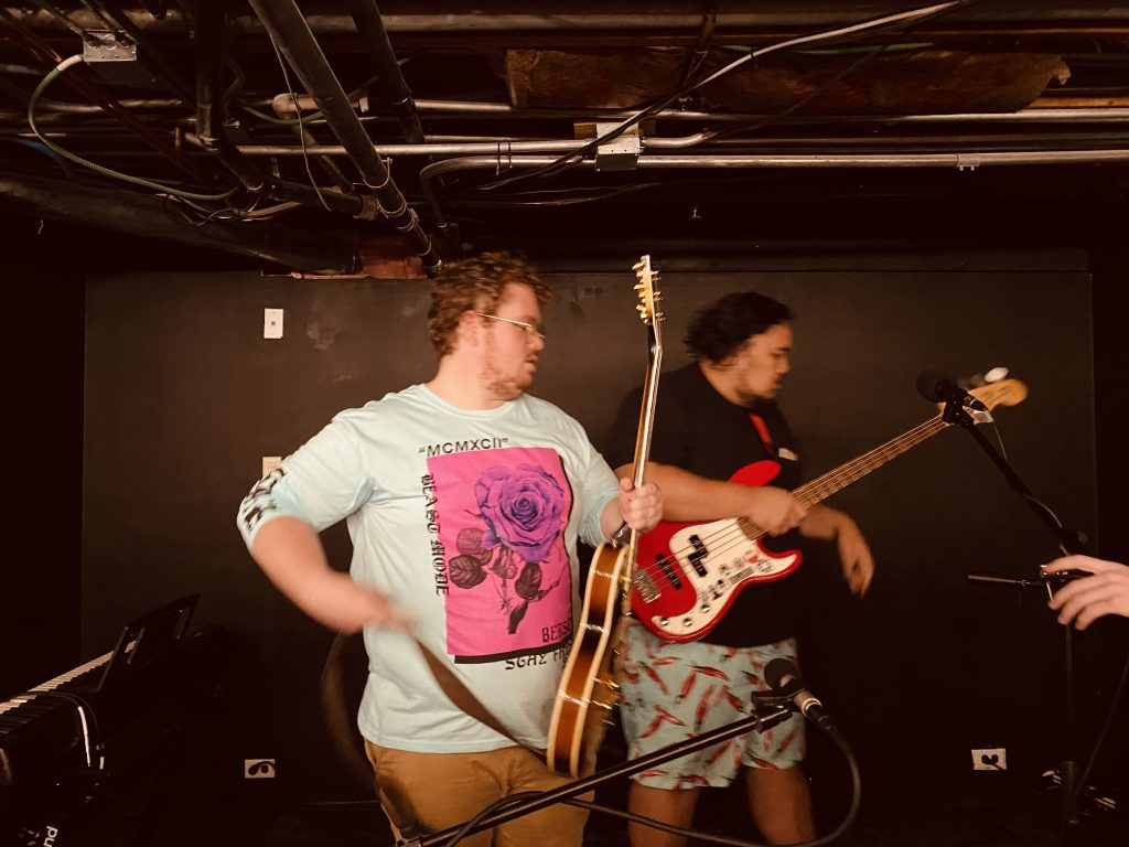 """Alec Mikesell and Sui singing together in a band with a name they made up that night, """"two big dudes""""."""