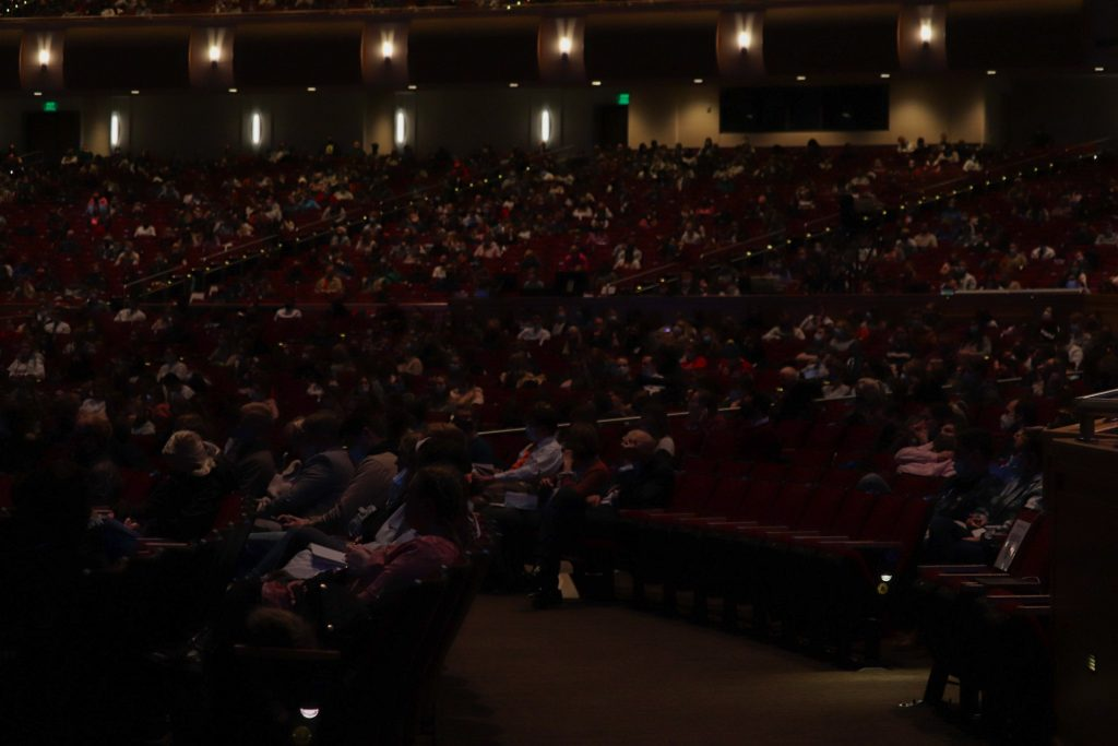 Students in the devotional crowd sit socially distanced.