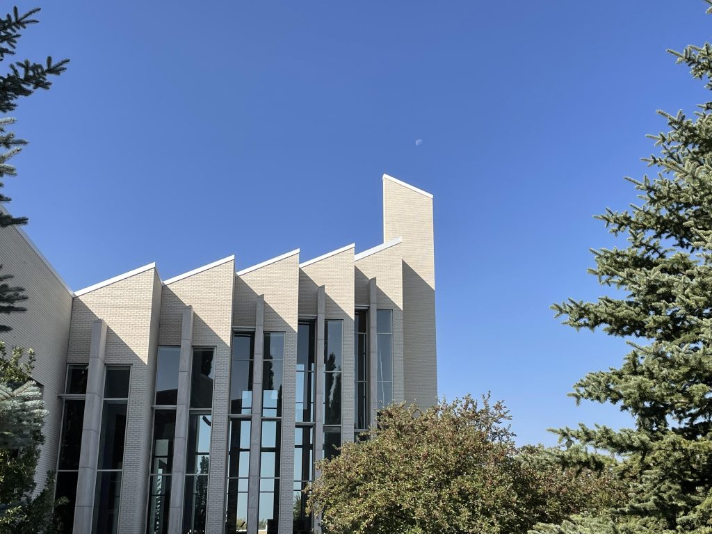 The Taylor Building sticks up into a clear blue sky. The moon is small but visible over the tallest spire. Trees border the image.