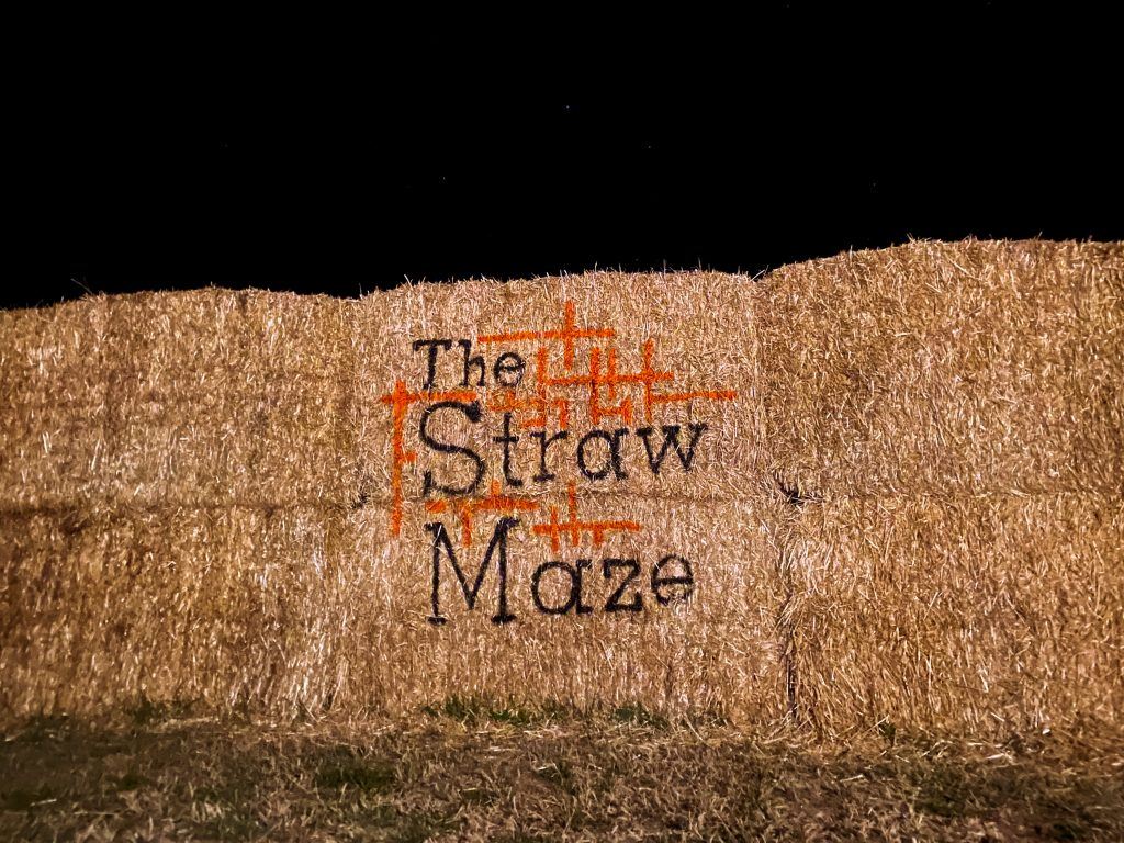 A stack of hay bales with The Straw Maze logo painted on the front.